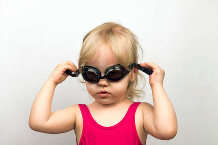 girl glasses: Little blond girl in a pink bathing suit cohesive wears goggles, studio photo