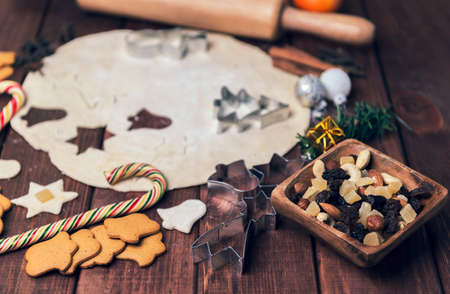 cashew tree: On a wooden desk background Christmas composition - candy cane, dough figurines, Christmas-tree branch Christmas balls, raisins, nuts, cinnamon sticks, cookies, star anise, mandarins bump roll out the dough layer plunger