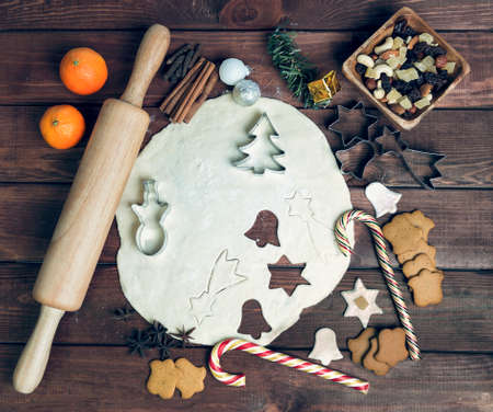 congratulations cards spice: On a wooden desk background Christmas composition - candy cane, dough figurines, Christmas-tree branch Christmas balls, raisins, nuts, cinnamon sticks, cookies, star anise, mandarins bump roll out the dough layer plunger