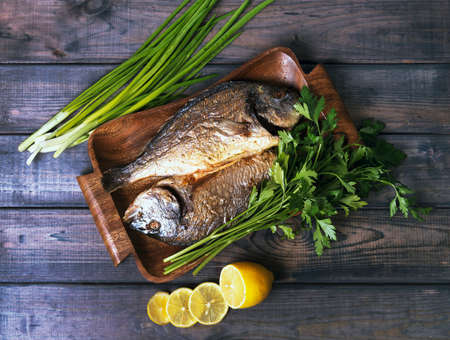 congratulations cards spice: On a wooden table plate with two roasted carp fish dorado with parsley, chives and lemon. Stock Photo