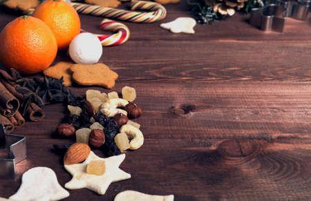 cashew tree: On a wooden desk background Christmas composition - candy cane, dough figurines, Christmas-tree branch Christmas balls, raisins, nuts, cinnamon sticks, cookies, star anise, mandarins bump