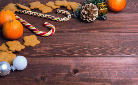 cashew tree: On a wooden desk background Christmas composition - candy cane, dough figurines, Christmas-tree branch Christmas balls, raisins, nuts, cinnamon sticks, cookies, star anise, mandarins bump