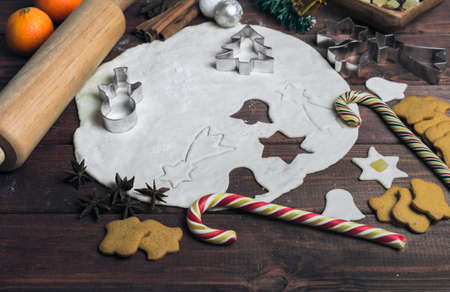 roll out: On a wooden desk background Christmas composition - candy cane, dough figurines, Christmas-tree branch Christmas balls, raisins, nuts, cinnamon sticks, cookies, star anise, mandarins bump roll out the dough layer plunger