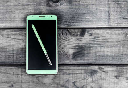 your text: On the wooden table is a smartphone and pen green color with white display, there are a place in your text or picture