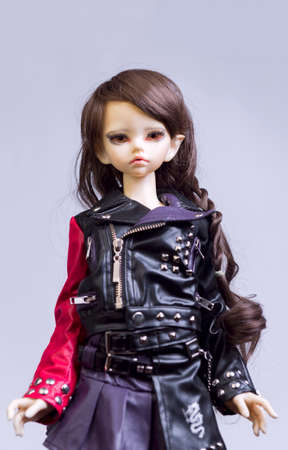jointed: MOSCOW, RUSSIA - November 14, 2015: On a wooden table smiling ball jointed doll girl vampire elf in black leather dress