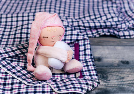 warm things: On a wooden table checkered flannel pajamas and a soft toy doll sleep man in a pink cap with a pillow in his hands