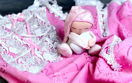 clothes interesting: On a wooden table delicate pink nightgown with lace and soft toy doll man sleep in a pink cap with a pillow in his hands