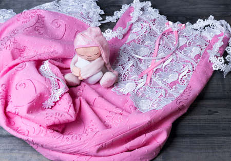 clothes interesting: On a wooden table delicate pink nightgown with lace and soft toy man sleep in a pink cap with a pillow in his hands Stock Photo