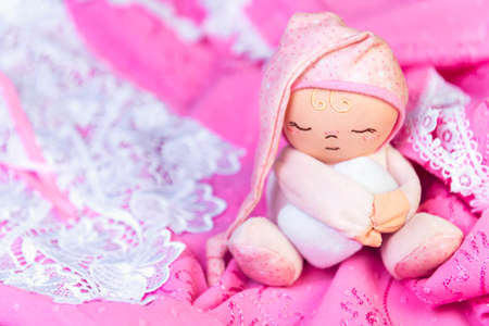 warm things: On a wooden table delicate pink nightgown with lace and soft toy man sleep in a pink cap with a pillow in his hands Stock Photo
