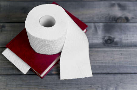 inodoro: On a gray wooden background hardcover red cover to read and white embossed roll of toilet paper for use in the toilet