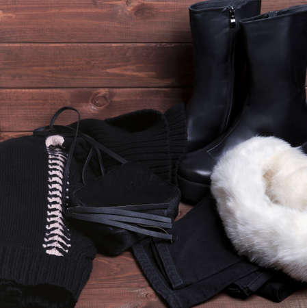On a brown wooden background winter black and white bow autfit for cold weather - wool knitted sweater with a volume-neck collar, black jeans, capri pants, a small bag over his shoulder, platform boots, fur bandage on his head Stock Photo
