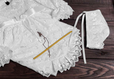 battesimo: Su un tavolo in legno di sfondo impostato per il battesimo del bambino - camicia, berretto, asciugamano, pannolini, candela, croce d'oro su una catena