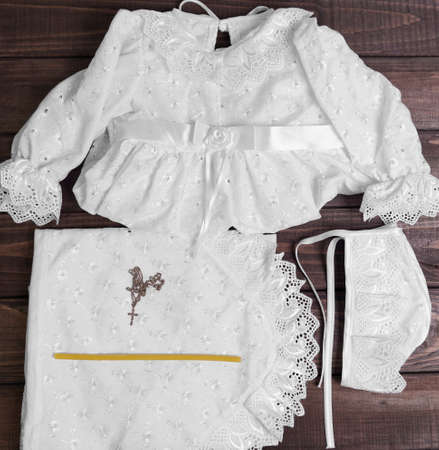 baptize: On a wooden background table set for the baptism of the infant - shirt, cap, towel, diaper, candle, gold cross on a chain Stock Photo