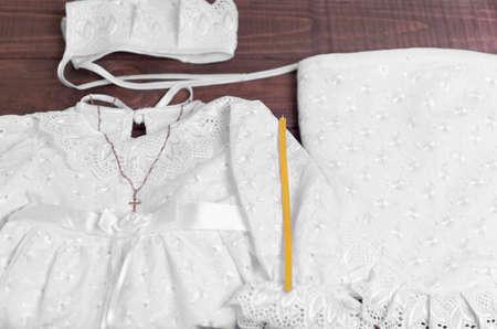 bautismo: En una mesa de madera de fondo establecido para el bautismo del beb� - la camisa, gorra, toalla, pa�ales, vela, cruz de oro en una cadena Foto de archivo