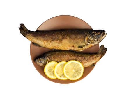 fish shop: On the wooden table is a plate with two baked fish trout with lemon