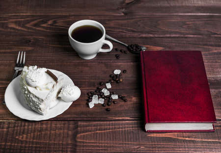 hard cover: On a wooden table delicacy - a saucer with a piece of cake and a cup of meringue with coffee beans and sugar, the book in a red hard cover, fork, spoon, there is an empty space for your text or image