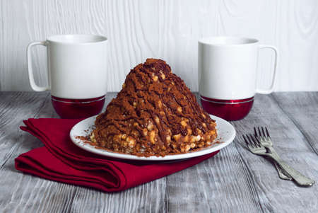 On a light wooden table in vintage style dessert for two cups of white-red, sand cake in the form of slides with cocoa, towel, napkin, fork