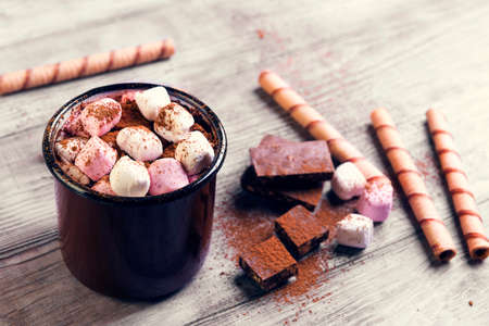 On a light wooden table metal mug with hot chocolate, pink and white marshmallow and cocoa sprinkles powdered chestnuts, there is an empty space for your text or image Stock Photo