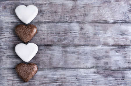 your text: On the bright background of shabby wooden gingerbread glazed white as valentine hearts for Valentines Day, there is a blank space for your text Stock Photo