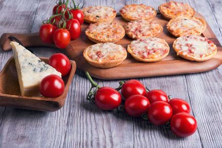 mini pizza: On a light wooden table background in rustic several mini-pizzas with ham and cheese, cherry tomatoes on a branch, a piece of blue cheese