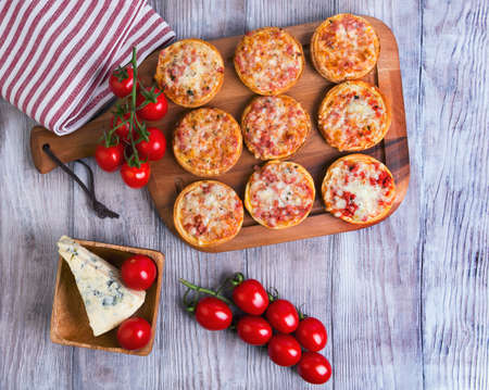 On a light wooden table background in rustic several mini-pizzas with ham and cheese, cherry tomatoes on a branch, a piece of blue cheese, top view