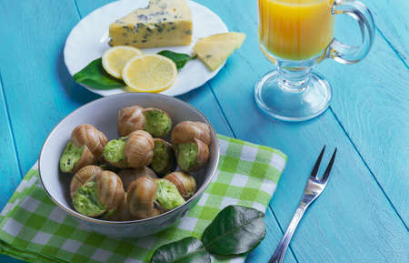 grape snail: On wooden table French food in Burgundy snail on a wooden tray with lime green leaves, blue cheese, chopped lemon slices, cloth towel