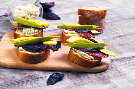 smoked sausage: On a light wooden table cooking small sandwiches tapas with avocado, cheese, smoked sausage, basil, bread Stock Photo