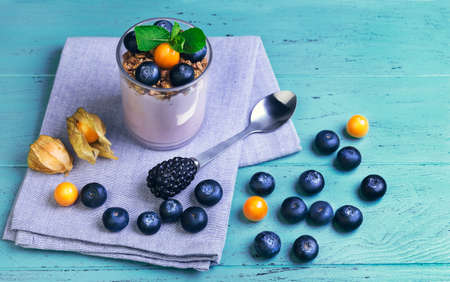 cape gooseberry: On a wooden blue background breakfast glass of yogurt, muesli, mint, blueberries and berries physalis, cotton cloth Stock Photo