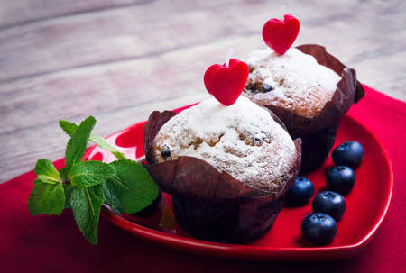 muffin: On wooden table in a bright red cloth with plate in the form of heart with two berry muffins with candles, sugar, blueberry, mint, card Happy Valentines Day