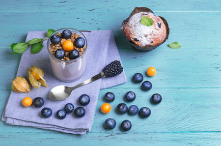 blueberry muffin: On blue wooden background Breakfast muffin berry, cape gooseberry, blueberry yogurt in a glass, sprig of mint, spoon with blackberry