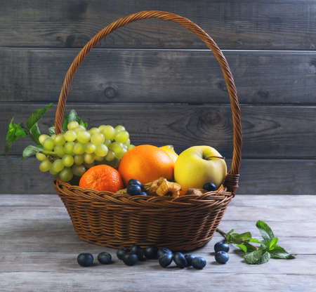 fruits in a basket: Wicker straw basket with an assortment of fruits and lemon, orange, grape, strawberry, berries Physalis, tangerine on a wooden table in a rustic style