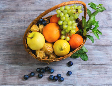 gift basket: Wicker straw basket with an assortment of fruits and lemon, orange, grape, strawberry, berries Physalis, tangerine on a wooden table in a rustic style, top view Stock Photo