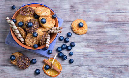 sweet background: On a light wooden background blue ceramic bowl with cookies, decorated with a dried orange circle with a stick of cinnamon, blueberry, chocolate rolls, cloth