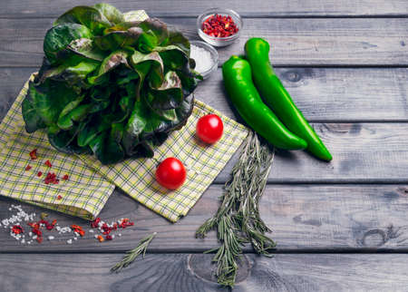entries: On a light wooden background ingredients fresh lettuce leaves salad, pepper, salt, cherry tomatoes, cloth, top view, blank space for your text entries, recipes