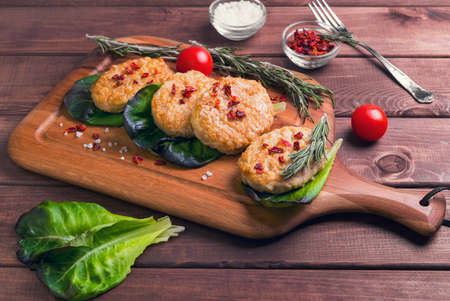 salt crystal: On a brown background wooden cutting board in a rustic style with meat chicken cutlet, red pepper petals sprig of rosemary, salt crystal, cherry tomatoes, lettuce, Fork