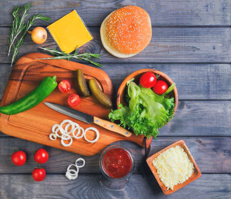 sprigs: Ingredients for cheeseburgers, onion, salted cucumbers, cherry tomatoes, ketchup sauce, melted cheese and grated, green pepper, rosemary sprigs on a cutting board on a dark wooden background, top view