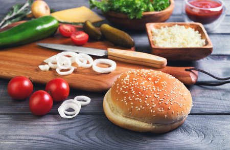 sprigs: Ingredients for cheeseburgers, onion, salted cucumbers, cherry tomatoes, ketchup sauce, melted cheese and grated, green pepper, rosemary sprigs on a cutting board on a dark wooden background