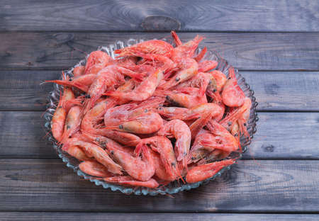un healthy: Large glass dish with a large frozen shrimp on wooden gray background in rustic style Stock Photo