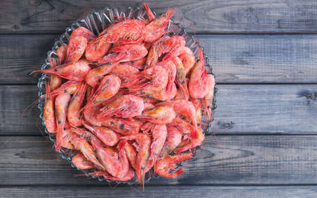 un healthy: Large glass dish with a large frozen shrimp on wooden gray background in rustic style, empty space for your text Stock Photo