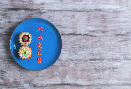 curlicues: Postcard Greetings from the International Womens Day March 8, on a light wooden background blue ceramic plate with two cakes Stock Photo