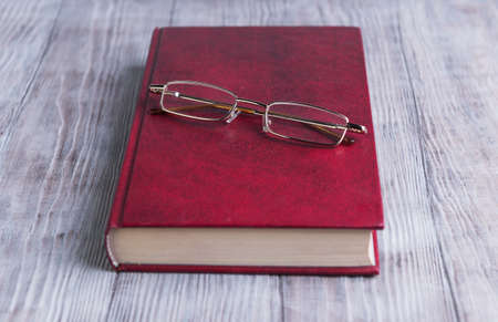 hard cover: On a light background is a wooden red book in hard cover and glasses for poor vision to read