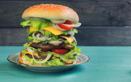 overeat: Big cheeseburger deluxe high on green wooden background in rustic style for gluttons