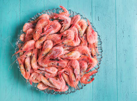 un healthy: Large glass dish with a large frozen shrimp on wooden blue-green background in rustic style, top view, empty space for your text