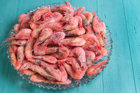 un healthy: Large glass dish with a large frozen shrimp on wooden blue-green background in rustic style Stock Photo