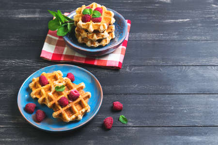Belgian lush round waffles with fresh raspberries, twigs and leaves mty in a blue ceramic plate and bowl on dark wooden background, empty space for your text 版權商用圖片