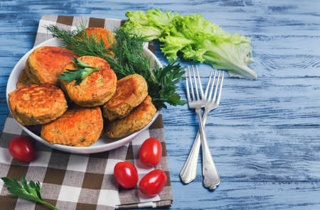 vegetable cutlets in a white porcelain bowl, parsley, dill, cherry tomatoes, lettuce, silver forks on a blue wooden background