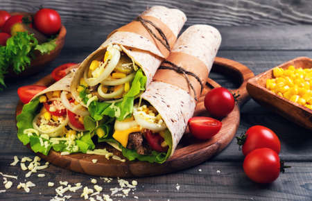 Sandwiches twisted roll Tortilla burritos three pieces on a wooden cutting board on a gray background, lettuce, cucumbers malosollnye, cherry tomatoes, corn, onion rings, meat Stock Photo