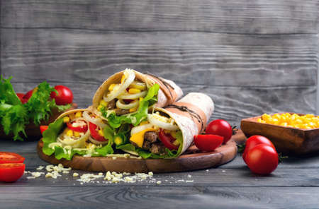 onion rings: Sandwiches twisted roll Tortilla burritos three pieces on a wooden cutting board on a gray background, lettuce, cucumbers malosollnye, cherry tomatoes, corn, onion rings, meat Stock Photo