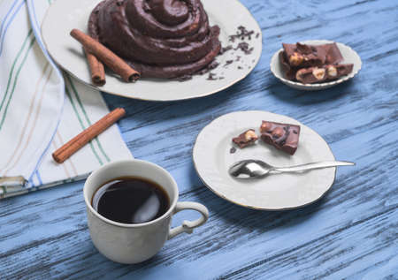 curlicues: Round Twisted Bun Danish snail poured chocolate icing, white cup of coffee espresso, cinnamon sticks, pieces of chocolate with hazelnuts on a blue wooden background