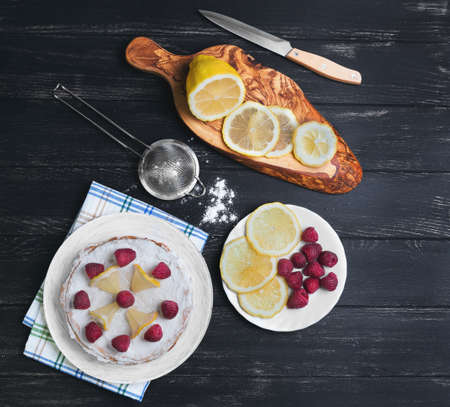 caterers: Lemon cake with raspberries, a cutting board with slices of lemon, sieve with icing sugar on a table of black color, top view